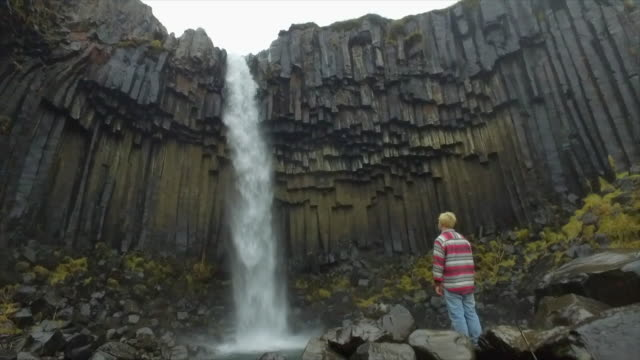 a man hiking near svartifoss waterfall in skaftafell in vatnajokull national park river flowing in iceland, europe. - slow motion - goodsportvideo stock videos and b-roll footage