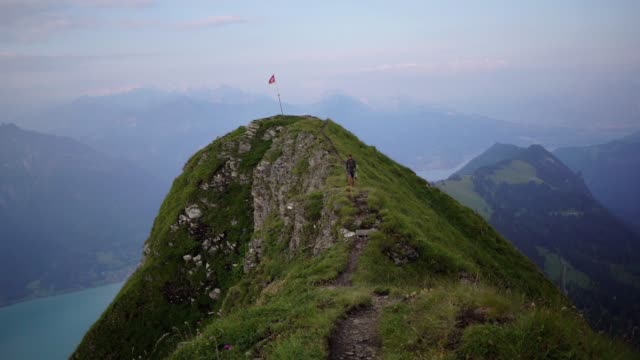 man hiking on the mountain ridge in swiss alps - approaching stock videos & royalty-free footage