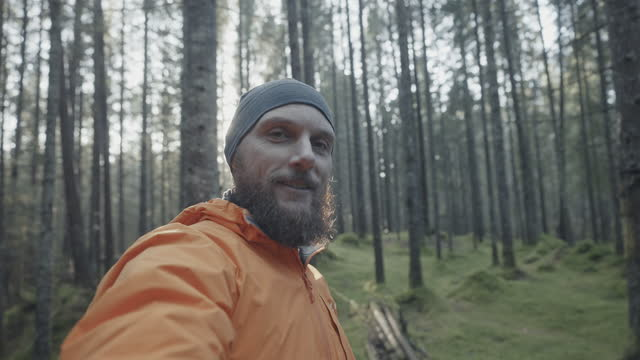 man hiking outdoors in springtime forest: vlogging with mobile phone - wilderness stock videos & royalty-free footage