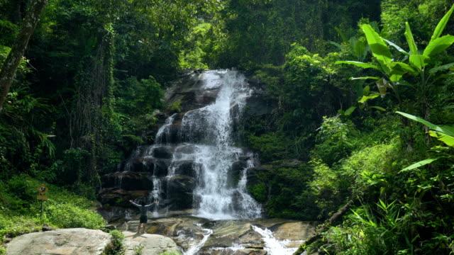 SLO MO Man hiking to tropical waterfall and raising arms up.