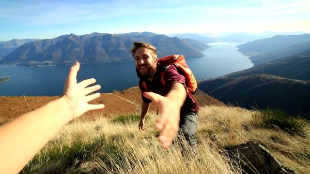 Mann Wandern bergauf, hand erreichen zu können