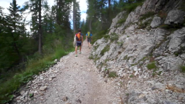 vídeos de stock, filmes e b-roll de a man hiking with a rock climbing rope on a trail in the mountains. - goodsportvideo