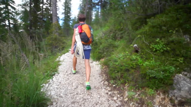 a man hiking with a rock climbing rope on a trail in the mountains. - climbing rope stock videos & royalty-free footage