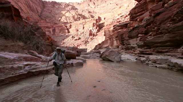 Man hiking with backpack through river in deep red rock desert slot canyon.