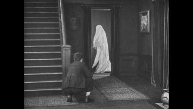1921 Man (Buster Keaton) hits bedsheet ghost on the head with a vase