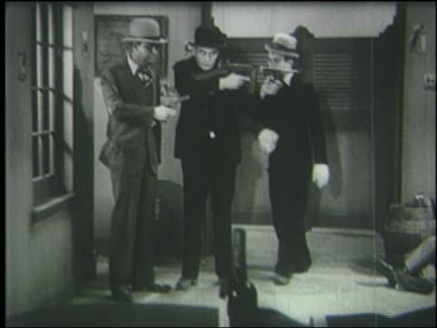 B/W 1933 man (Harry Langdon) hits man holding machine gun who falls down shooting