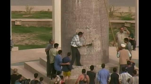 man hitting at stone column with hammer crowds gathered around statue of saddam hussein us flag on saddam statue - saddam hussein stock videos & royalty-free footage