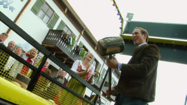 ms man hitting button of high striker game at oktoberfest fair, munich, germany - fairground stall stock videos & royalty-free footage