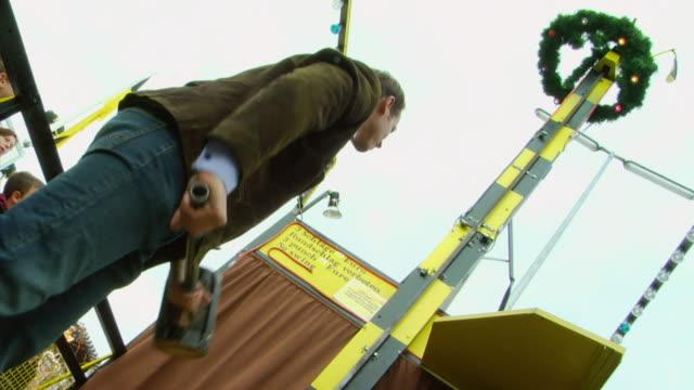 MS Man hitting button of high striker game at Oktoberfest fair, Munich, Germany