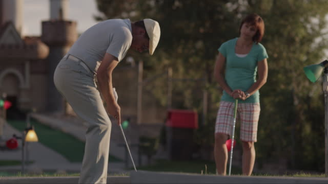 MS TS Man hitting golf ball into hole and cheering / Orem, Utah, USA