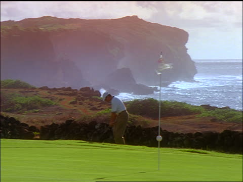 man hitting golf ball onto green with flag in foreground / ocean + cliffs in background / poipu bay resort, kauai - golf flag stock videos & royalty-free footage