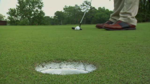 SLO MO CU Man hitting golf ball past hole on golf course / Atlanta, Georgia, USA