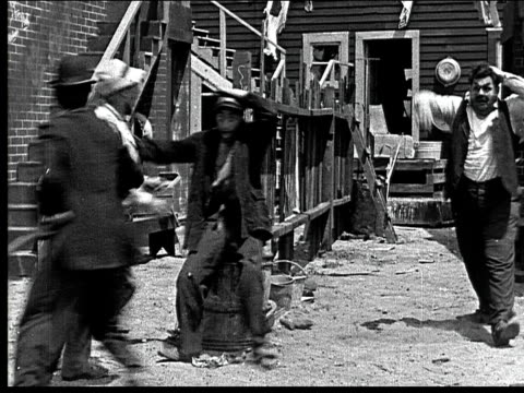 1918 b/w man hitting three other men with mallet/men chasing him around fence - mallet hand tool stock videos and b-roll footage