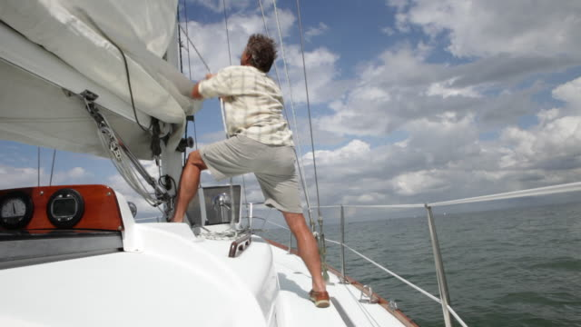 cu man hoisting sail on moving yacht /tampa,florida,usa - hoisting stock videos & royalty-free footage