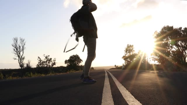Man hoists backpack, walks along paved road