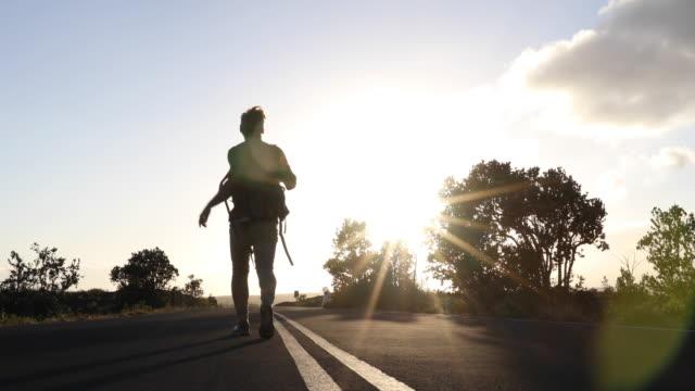 man hoists backpack, walks along rural road at sunrise - hochziehen stock-videos und b-roll-filmmaterial