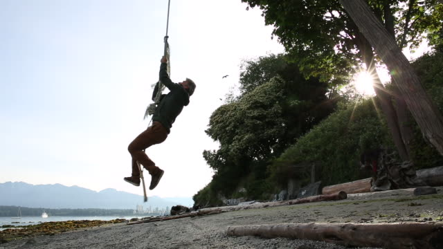 man hoists himself up rope swing, from beach below - rope swing stock videos & royalty-free footage
