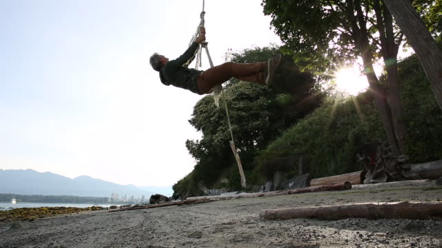 man hoists himself up rope swing, from beach below - rope swing stock videos & royalty-free footage