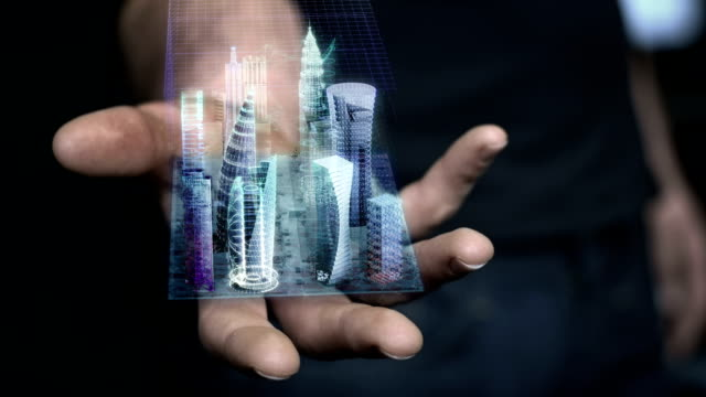man holding 3d city hologram in his hand - futuristico video stock e b–roll