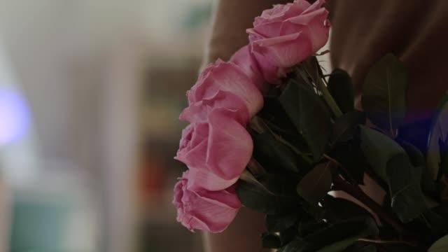 vidéos et rushes de homme retenant un bouquet de roses derrière son dos pour surprendre sa femme - bouquet de fleurs