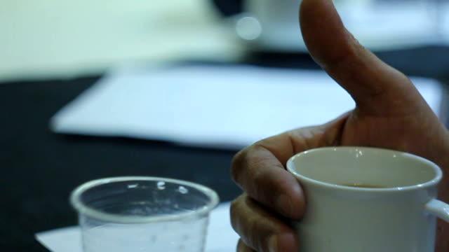 vidéos et rushes de homme tenant un chapeau de thé à la réunion au sommet de matin - tasse