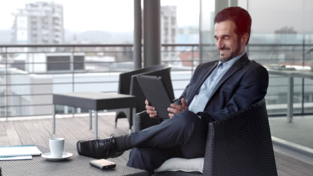 Man holding a digital tablet and smiling while sitting in a rooftop lounge in the city