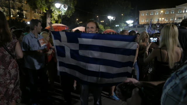 teaching democracy teaching pride and teaching honor views of greek parliament in the background crowds of people waving greek flags after referendum... - ユーロ圏債務危機点の映像素材/bロール
