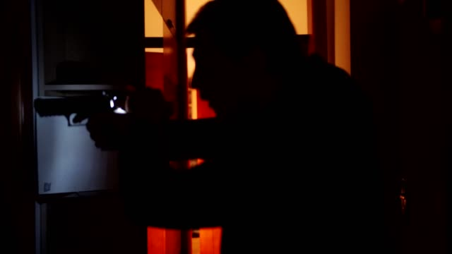 a man holding a gun and searching around the house - inspector stock videos & royalty-free footage