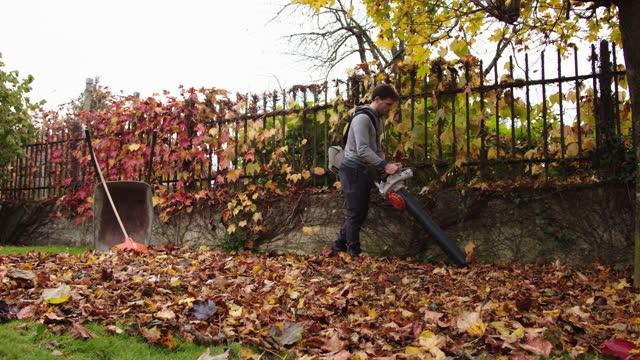 stockvideo's en b-roll-footage met mens die een bladvacuüm houdt, dat de tuin van gevallen bladeren schoonmaakt - herfst