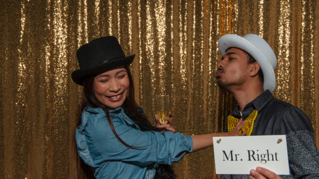 """man holding a """"mr. right"""" sign taking photos with a woman in the photo booth - western script stock videos & royalty-free footage"""