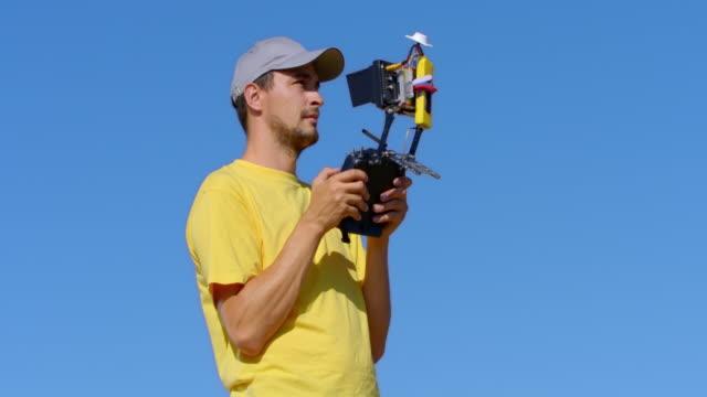 ドローンを動作しているときにリモート ユニットを保持している男 - テレビのリモコン点の映像素材/bロール