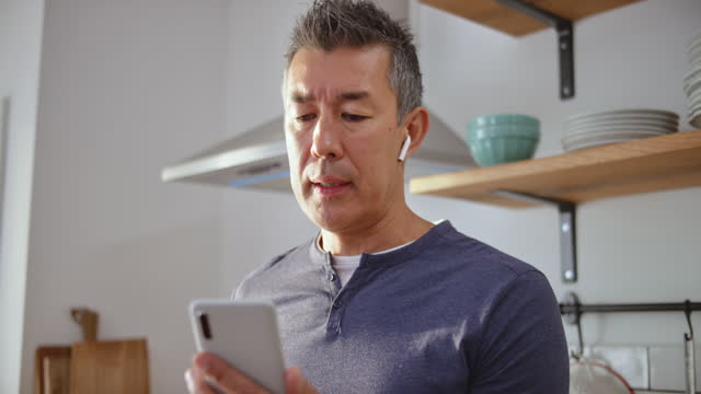 slo mo man holding a smartphone in his kitchen and having a videoconference call - part of a series stock videos & royalty-free footage