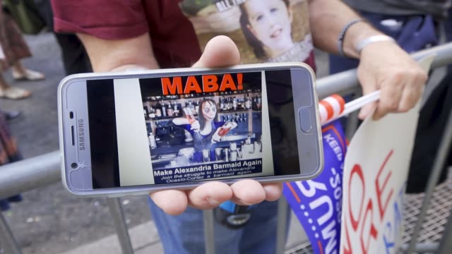 Man holding a smartphone with a picture of Alexandria OcasioCortez as a Barmaid and the acronym 'MABA' In a rally titled 'Ilhan Omar Must Go' Jews...