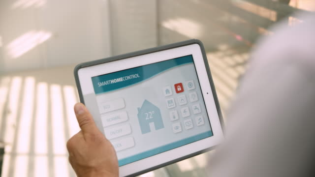 man holding a tablet and setting the heating with the smart home app - home automation stock videos & royalty-free footage
