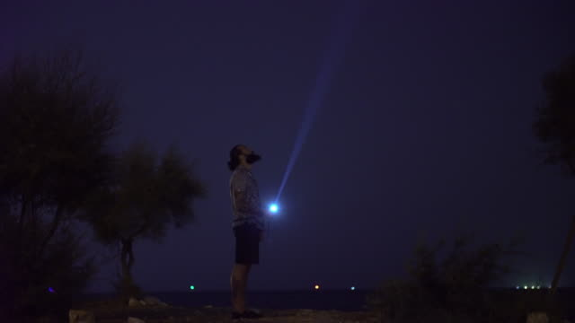 a man holding a torch to the dark sky - electric torch stock videos & royalty-free footage