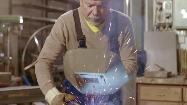 vídeos de stock, filmes e b-roll de slo mo man holding a welding mask while working - soldador