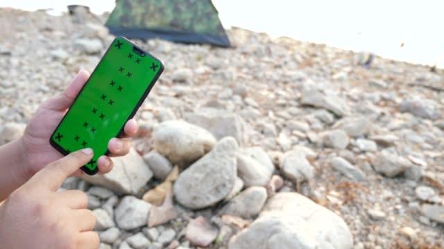 vídeos de stock, filmes e b-roll de homem que prende e que desrola o telefone esperto com a tela verde mock-up na área de acampamento com praia rochosa - modelo web