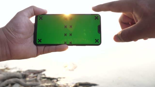vídeos de stock, filmes e b-roll de homem que prende e que desrola o telefone esperto com a tela verde mock-up com fundo de sun - modelo web