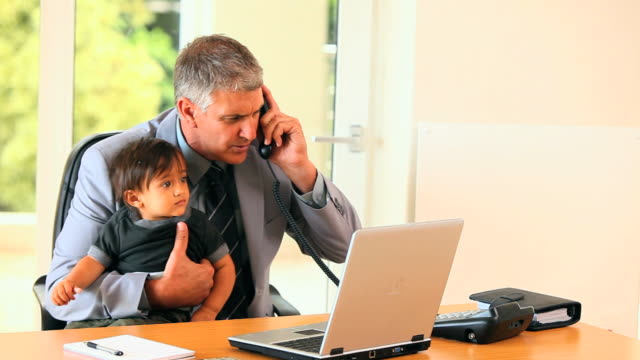 vídeos de stock, filmes e b-roll de man holding baby and answering phone at desk / cape town, western cape, south africa - telefone fixo