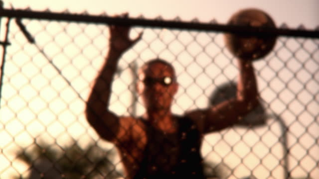 ms shaky man holding basketball standing behind chain link fence, jacksonville, florida, usa - human limb stock videos & royalty-free footage