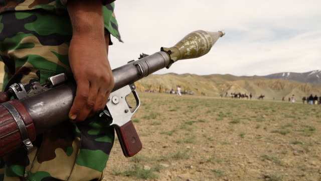 man holding bazooka gun watches group of men play horse mounted game. - rocket launcher stock videos & royalty-free footage
