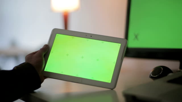 Mann, der leere Tablet-PC vor Green-Screen hält.