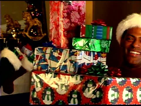 vídeos de stock e filmes b-roll de man holding christmas presents - chapéu do pai natal