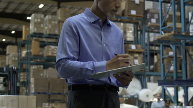 man holding clip board and stocktaking, man pulling hand operated pallet truck in background of warehouse - hubwagen stock-videos und b-roll-filmmaterial