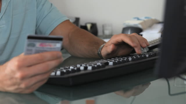 vídeos de stock e filmes b-roll de cu r/f man holding credit card typing on keyboard, jersey city, new jersey, usa - compra online