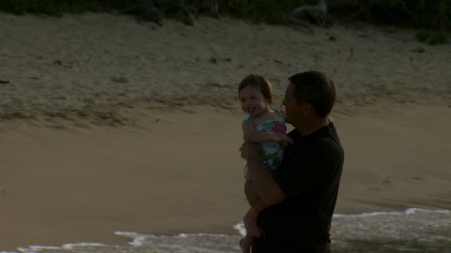 man holding daughter in water at beach - see other clips from this shoot 1141 stock videos & royalty-free footage