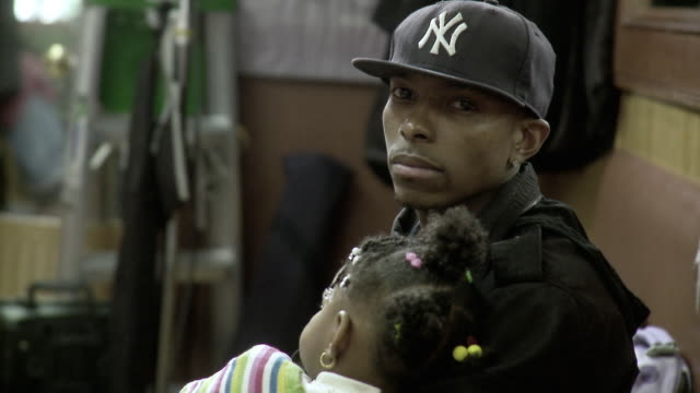 vidéos et rushes de ms man holding daughter (18-23 months) on lap sitting at barbershop, brooklyn, new york city, new york state, usa - famille monoparentale