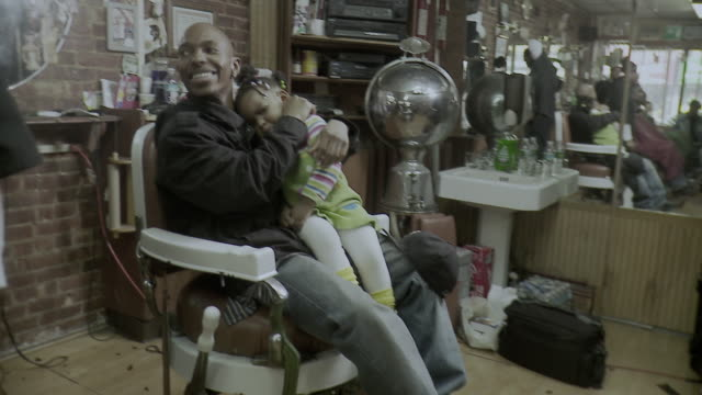 ms zi man holding daughter (18-23 months) on lap sitting in barber chair, brooklyn, new york city, new york state, usa - 18 23 months bildbanksvideor och videomaterial från bakom kulisserna