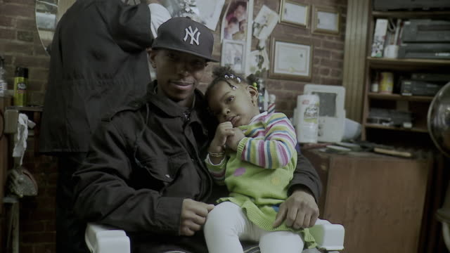 vidéos et rushes de ms man holding daughter (18-23 months) on lap waiting at barbershop, brooklyn, new york city, new york state, usa - 20 24 ans