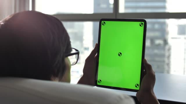 Mann hält Digital Tablet in der Hand und Blick auf Tablet PC green screen
